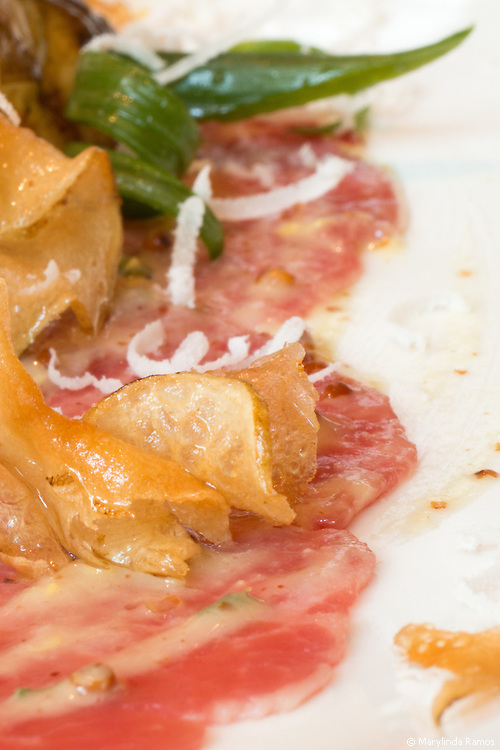 Beef Carpaccio gets a rustic twist with paper-thin potato crisps, sunchoke, green onion, pecorino, and mustard vinaigrette