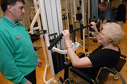 Woman wheelchair user with instructor using weights at an inclusive fitness gym,
