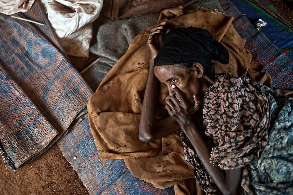 Kenya, Dadaab, le 13-08-11 - camp Ifo 3. Il accueille plus de 400 000 personnes, Dabaab est le plus grand camp de réfugiés au monde.  Ce sont pour la plupart des Somaliens (95%) ayant fuit la guerre et la famine, deux fléaux qui sévissent dans leur pays. Une femme se laisse mourir de faim dans la tente familiale. Ses proches n'ont plus d'espoir pour elle.