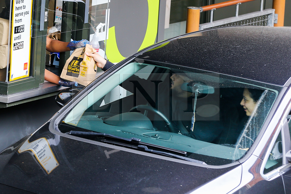 © Licensed to London News Pictures. 04/06/2020. London, UK. A staff member wearing plastic gloves hands a meal bag to a customer at McDonald's Drive Thru in north London. McDonald's Drive Thru opens in Haringey after lockdown restrictions are relaxed. Photo credit: Dinendra Haria/LNP