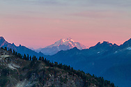 The last few minutes of sunset light on Glacier Peak in the North Cascades. Photographed from the Chain Lakes Trail in the Mount Baker Wilderness in the North Cascades of Washington State, USA.