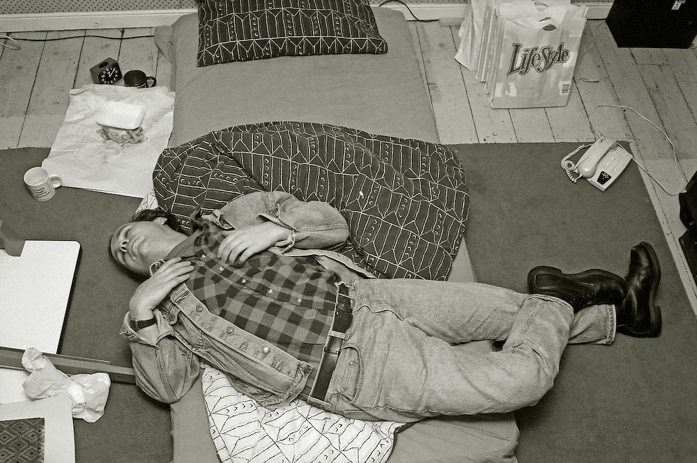 A man sleeps across a mattress in an untidy room. Various objects scattered around testify to his bohemian lifestyle [serendipitously, that word appears on a carrier bag in the corner]