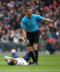 Referee Andre Marriner checks on Tottenham Hotspur's Harry Winks after a collision during the Premier League match at Wembley Stadium, London.