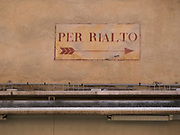 Street sign painted on a wall indicating the direction to the Rialto Bridge