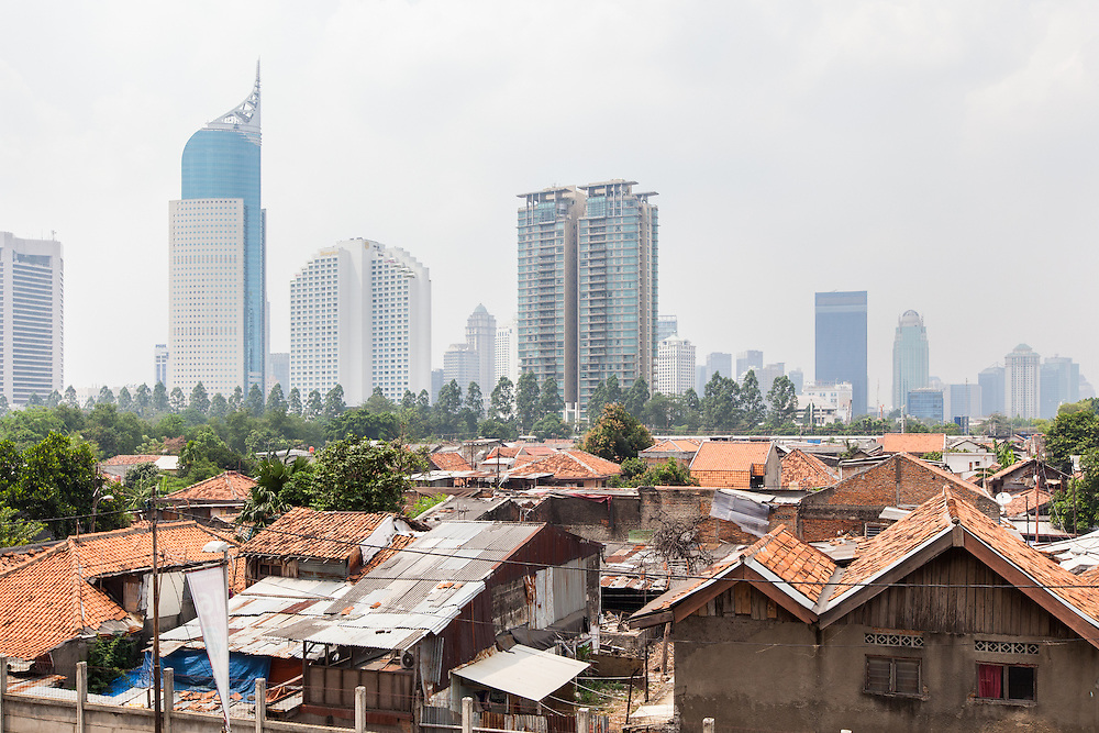 A residential neighborhood in Jakarta.  In the background is the BNI Tower and the Shangri-La 5-star Hotel. <br /> <br /> Despite the slowdown in the economy prices and rents are still rising in Jakarta.  Nevertheless, no big project have stopped.  The pace of construction is slow since the city has thousands of acres of one and two-story houses with multiple owners and no easy way to purchase and redevelop them.  September 20, 2013.