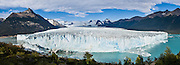 Visit Perito Moreno Glacier in Los Glaciares National Park as a day trip from El Calafate, in southwest Santa Cruz province, Argentina. Easy boardwalks give wide views of Moreno Glacier, an impressive wall of ice 200 feet high and 3 miles (5 km) wide flowing into Lake Argentina. The glacier flows up to 2300 feet thick and originates in the huge Hielo Sur (Southern Icefield) in the southern Andes mountains. For the past 90 years, its advancing has equaled melting (up to 2 meters per day, 700 meters per year), and the terminus has stayed at one location. Flowing ice periodically dams an arm of the lake which rises for a few years then breaks across the nose of the glacier as a crashing river (in March 2004 and 1991). In this 2005 photo, a narrow river flowed across the glacier face which calved large chunks of ice into the water with a loud crash several times per day. The foot of South America is known as Patagonia, a name derived from coastal giants, Patagão or Patagoni, who were reported by Magellan's 1520s voyage circumnavigating the world and were actually Tehuelche native people who averaged 25 cm (or 10 inches) taller than the Spaniards. Panorama stitched from 4 overlapping photos.