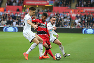 Elias Kachunga of Huddersfield Town © is challenged by Leon Britton of Swansea city (r) and Federico Fernandez of Swansea city (l). . Premier league match, Swansea city v Huddersfield Town at the Liberty Stadium in Swansea, South Wales on Saturday 14th October 2017.<br /> pic by  Andrew Orchard, Andrew Orchard sports photography.