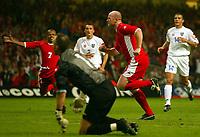 Photograph: Scott Heavey.<br />Euro 2004 Group 9 Qualifying match.<br />Wales v Serbia and Montenegro. 11/10/2003.<br />John Hartson celebrates bringing Wales level