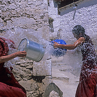 Tibetan Buddhist monks engage in a playful waterfight at a monastery in Tibet.