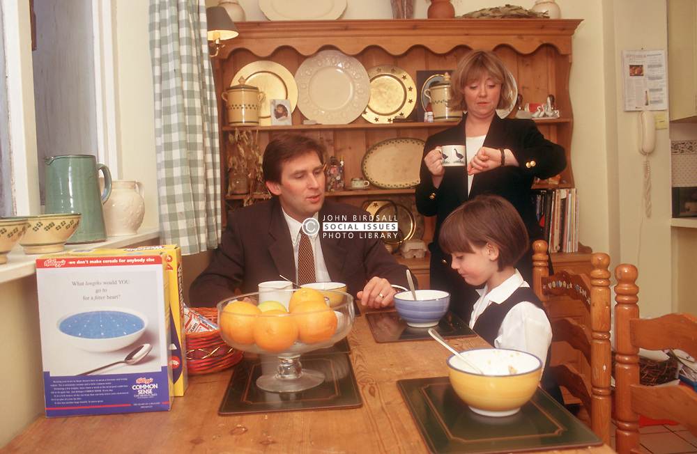 Mother preparing to leave for work; with father and daughter sitting at kitchen table finishing breakfast,