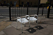 Strange scene of two modern commode chairs sitting discarded on a street in London, England, United Kingdom. A commode is the standard term for a chair, often on wheels, enclosing a chamber pot, as used in hospitals and the homes of invalids
