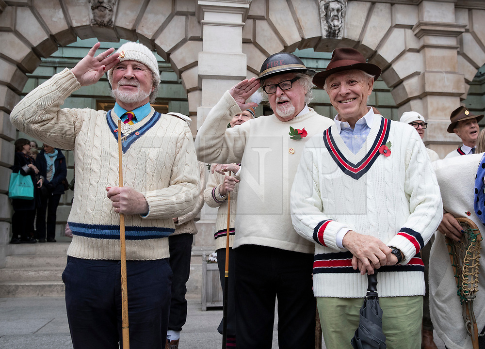 """© Licensed to London News Pictures. 09/11/2018. London, UK.  To mark Remembrance Day, members of the""""Unshrinkables"""" gather ahead of a drill practice in the Royal Academy of Arts Courtyard. At the outbreak of WW1 in 1914, the original members of the United Arts Rifles – a volunteer force comprised of artists from the Chelsea Arts Club – responded to a call to duty. The group didn't have uniforms, so they bought their own """"unshrinkable"""" white woollen jumpers and hats, and drilled using wooden planks and broomsticks instead of guns. They paraded in the courtyard of the Royal Academy, and were given use of some of the galleries as a mess. The group has been in existence since 1914, and each Remembrance Day the members gather together to parade in the courtyard of The Royal Academy. Photo credit: Peter Macdiarmid/LNP"""