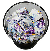 Banknotes in a waste paper basket On white Background