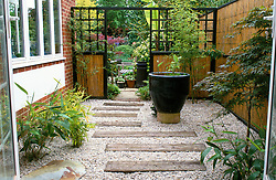 Side passage designed in oriental style divided by trellis and bamboo screen from rest of garden. Water feature planted with Thalia dealbata. Path of railway sleepers set into gravel