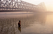 It is dawn in Calcutta, West Bengal, India and on the West bank of the Hooghly River the sun is rising from across the Howrah Bridge. A man has waded out into waist-deep water and stands in the polluted river saying his prayers and offering thanks to his Hindu Gods. He has found inner-peace, a tranquillity surrounded by the chaotic pace of Indian life in this city. The engineering of the bridge stretches across the water as the humanity cross to their businesses and markets. The bridge is one of three on the Hooghly River and is a famous symbol of Kolkata and West Bengal. Bearing the daily weight of approximately 150,000 vehicles and 4,000,000 pedestrians. It is one of the longest bridges of its type in the world. The Hooghly River is an approximately 260 km long distributary of the Ganges River.