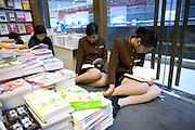 A pair of young women in uniforms take a break to read at a book shop in Shanghai. China's state media said recently that nearly half of the media products such as books, films, music CDs and software bought by Chinese consumers in 2005 were pirated.
