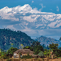 The Himalaya rise behind a family farm in the foothills of Nepal.