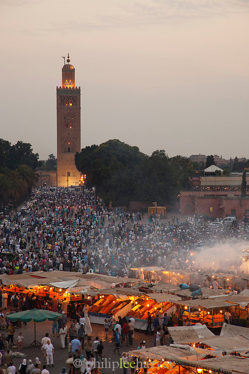 The minaret of the Koutoubia Mosque, towering over hundreds of people walking between food stalls, in the Djemaa el Fna in the medina of Marrakech, Morocco. Every night the main square fills with dozens of food vendors and their carts
