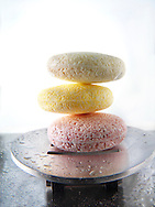 Bars of  coloured hand made scented soaps piled in a modern metal soap dish.
