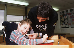 Carer feeding young child with disability; who is wheelchair user,