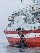 In the Southern Ocean offshore from the Antarctic Peninsula, passengers board a red and white cruise ship from a Zodiac boat, in snowy weather.