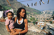 MOTHERS AND BABIES. Rocinha Favela, Rio de Janeiro, Brazil, South America. Mothers and children on the rooftops overlooking the favela and Rio. Although Rocinha is technically classified as a neighborhood, many still refer to it as a favela. It developed from a shanty town into an urbanized slum. Today, almost all the houses in Rocinha are made from concrete and brick. Some buildings are three and four stories tall and almost all houses have basic sanitation, plumbing, and electricity. Compared to simple shanty towns or slums, Rocinha has a better developed infrastructure and hundreds of businesses. There is also lots of deliquency, crime and drugs in the favelas.