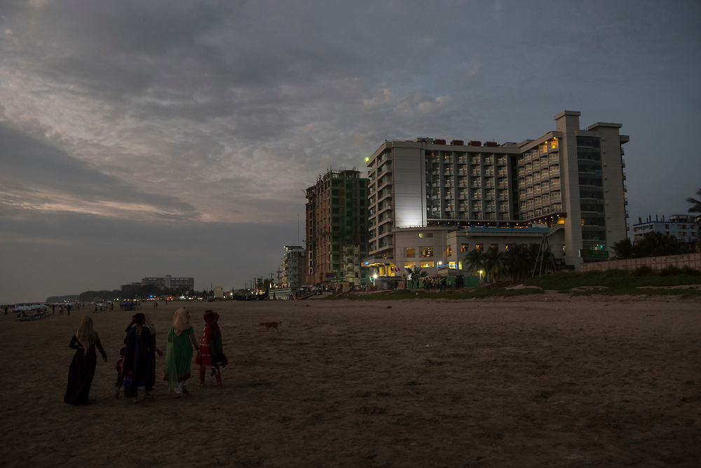 Women and children walk on the beach at dusk in Cox's Bazar, Bangladesh. The city is a popular tourist destination as well as fishing port and district headquarters.