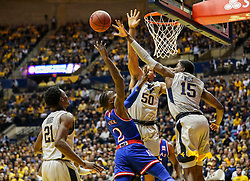 Jan 15, 2018; Morgantown, WV, USA; Kansas Jayhawks guard Lagerald Vick (2) shoots in the lane while defended by West Virginia Mountaineers forward Lamont West (15) and West Virginia Mountaineers forward Sagaba Konate (50) during the first half at WVU Coliseum. Mandatory Credit: Ben Queen-USA TODAY Sports