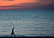 Man takes sunset stroll at Anna Maria Island, Florida, United States of America