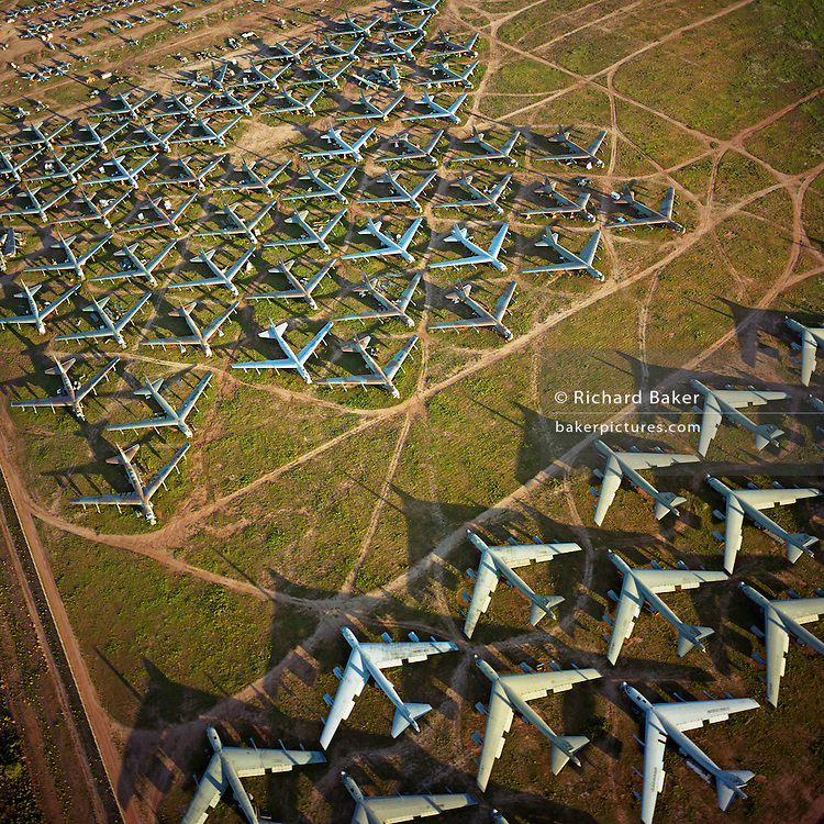 Seen from the air at dawn, the last remaining B-52 bombers from the Cold War-era are laid out in grids across the arid desert near Tucson Arizona. These retired aircraft whose air frames are too old for flight are being recycled, their aluminium worth more than their sum total. In the nuclear arms treaties of the 80s, Soviet satellites proved their decommissioning by spying the tails had been sliced apart huge guillotines and set at right-angles. This is a scene of confrontation, with opposing forces apparently facing each other in the way that Soviet and western armies fought the war of propaganda. Picture from the 'Plane Pictures' project, a celebration of aviation aesthetics and flying culture, 100 years after the Wright brothers first 12 seconds/120 feet powered flight at Kitty Hawk,1903..