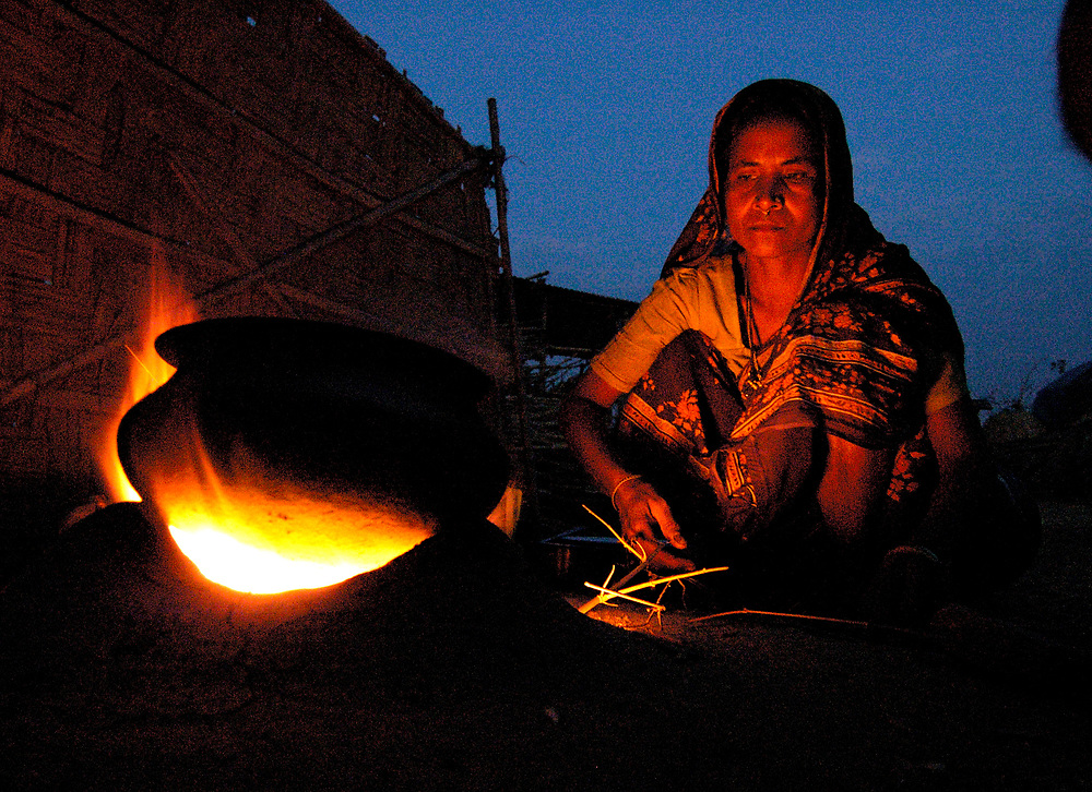 A woman in Tukura Partguan, a small village in India's Assam province, cooks her family's food over a dung-fueled fire.