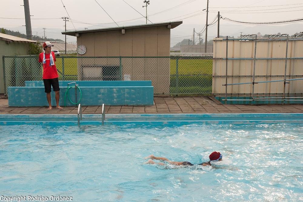 A lifeguard watches the pool at Yonesaki Primary School in Rikuzentakata, Japan, as girls swim.