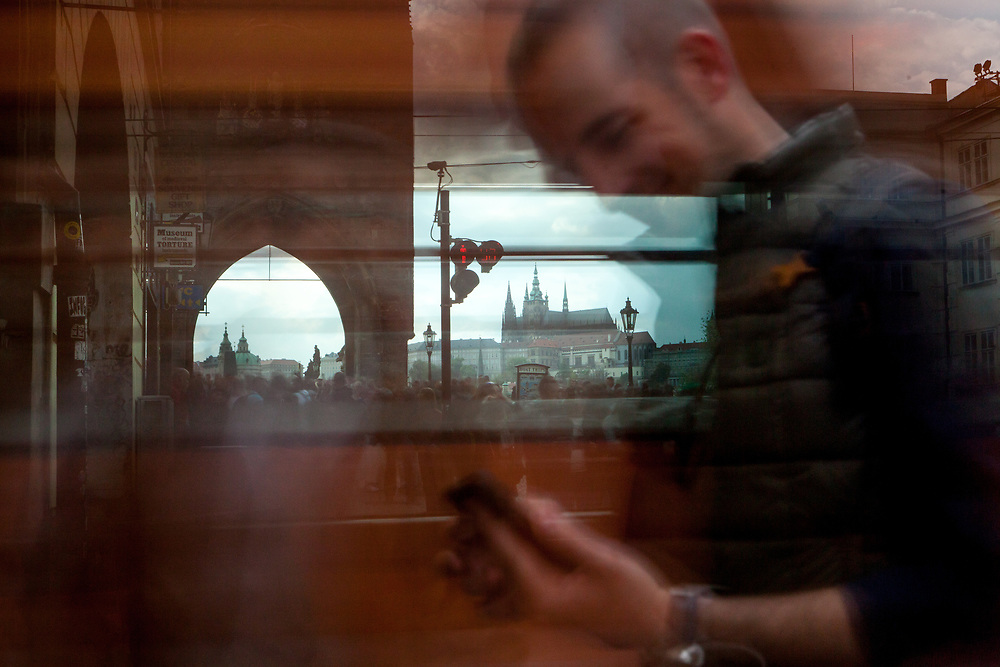 """A man sitting in a tram looking at his mobile device. In the back a crowd moving from the beginning of Charles Bridge towards """"Lesser Town"""" (Mala Strana) and Prague Castle."""