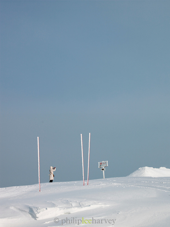 A tourist photographing on top of a snowy hill in Daisetsuzan National Park, Hokkaid?, Japan