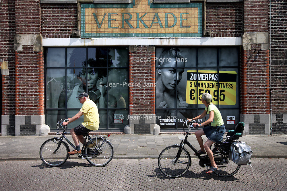 Nederland, Zaandam , 6 juli 2013.<br /> Wandeling door de binnenstad van Zaandam.<br /> Starten bij De Werf aan de Oostzijde. Daarvandaan kun je lopen op een soort boulevard tussen de flats en het water. De eerste stop is De Fabriek, filmhuis en eetcafé met terras aan de Zaan met uitzicht op de sluis. Daarna de sluis zelf.<br /> Dan langs het winkelgebied richting de Koekfabriek: Het oude Verkade pand dat is verbouwd en waar nu de bieb en sportschool en restaurant etc. in zitten.<br /> (Dat is aan de overkant van het startpunt) en misschien nog de Zwaardemaker meepakken aan de Oostzijde. Dat is een oud pakhuis die Rochdale enige jaren geleden heeft verbouwt tot appartementen met een stukje Nieuwbouw.<br /> Ook doen: het Russische buurtje vlakbij de Zaan. Dit jaar staat Rusland in de schijnwerpers en Zaandam heeft een speciale band met Rusland, vanwege het Czaar Peterhuisje en de Russische buurt. <br /> Op de foto: fietsend langs de Verkade fabriek.<br /> Foto:Jean-Pierre Jans