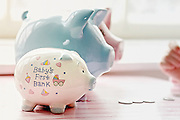 Financial planning. Baby's first bank. Three piggy banks stand one behind the other with coins visible on pink table. Part of hand is visible right side of frame.