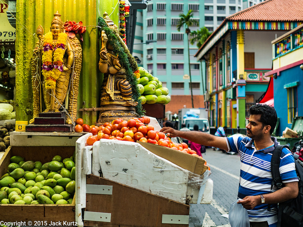 27 DECEMBER 2015 - SINGAPORE, SINGAPORE:   A man buys tomatoes at a produce shop on Buffalo Road across from Tekka Market. First opened in 1915, the market was moved to its present location in 1982 and renovated in 2009. It is one of the most famous hawker stall (street food) areas in Singapore.      PHOTO BY JACK KURTZ