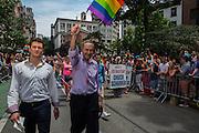 "Senator Charles Ellis ""Chuck"" Schumer, senior U. S. Senator from New York, wearing a lilac shirt, waves a rainbow flag in the parade on Christopher Street."