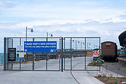 A sign saying 'Please keep a safe distance, this if for your safety and other' installed on the entrance gates to Folkestone Harbour Arm on the 4th of June 2020, Folkestone, United Kingdom.  The harbour Arm in Folkestone re-opened when Pubs and bars re-opened after lockdown.