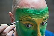 Living statue Mark Tate prepares his make up before a shift as the Green Man in a quiet place under the iconic Southbank concrete architecture. The process, which Mark takes great care over in every detail, takes approximately 45 minutes. The South Bank is a significant arts and entertainment district, and home to an endless list of activities for Londoners, visitors and tourists alike.