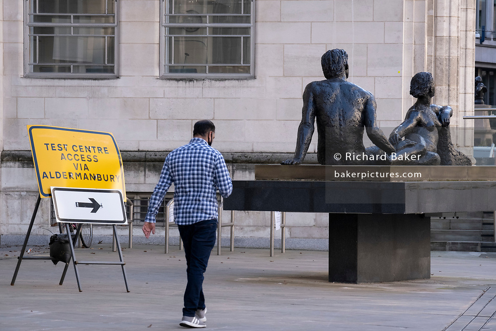 A Covid Testing Centre sign points those requiring a Coronavirus test, past the sculpture entitled Beyond Tomorrow by Karin Jonzen, and around the corner of the Guildhall in the City of London, the capital's financial district, on 9th March 2021, in London, England. Karin Margareta Jonzen, née Löwenadler, (1914 – 1998) was a British figure sculptor whose works, in bronze, terracotta and stone, were commissioned by a number of public bodies in Britain and abroad.
