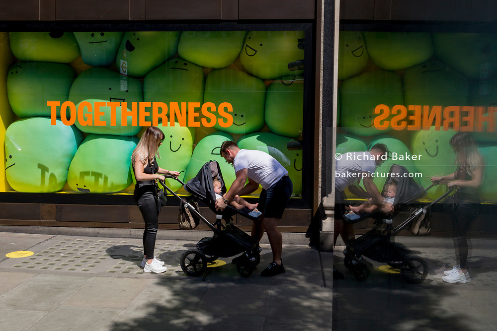 "In the 24hrs that a further 38 died from Coronavirus, bringing the total to 41,736, a further easing of the UK's Covid pandemic lockdown restrictions took place with many high street shops today being allowed to re-open after three months of forced closure. Prime Minister Boris Johnson, wanting to stimulate the economy, has urged people to ""shop with confidence"" and long queues formed outside the main brands. But unlike on public transport, face coverings are not compulsory so shop floors and shopping practices have had to be adapted to ensure customers' social distances, amid fears of a second infection wave. A family queue outside Selfridges on Oxford Street where window messages such as 'Togetherness' and of comfort can be read by waiting shoppers, on 15th June 2020, in London, England."