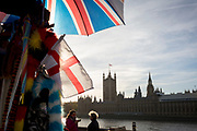 On the day that Prime Minister Theresa May petitions her cabinet on the current negotiations to leave the EU, the UK and English flags hang at a tourist souvenir stall opposite the Houses of Parlament on the river Thames, on 14th November 2018, in London, England.