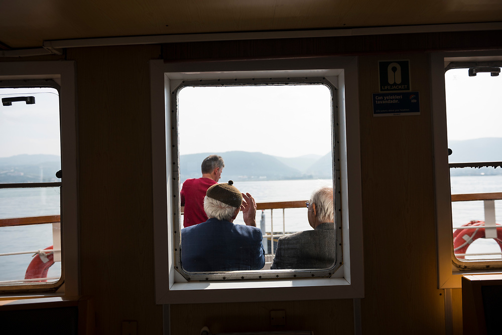 View through a window aboard a ferry of two old Turkish men talking as the ferry crosses the Gulf of Izmit, Turkey