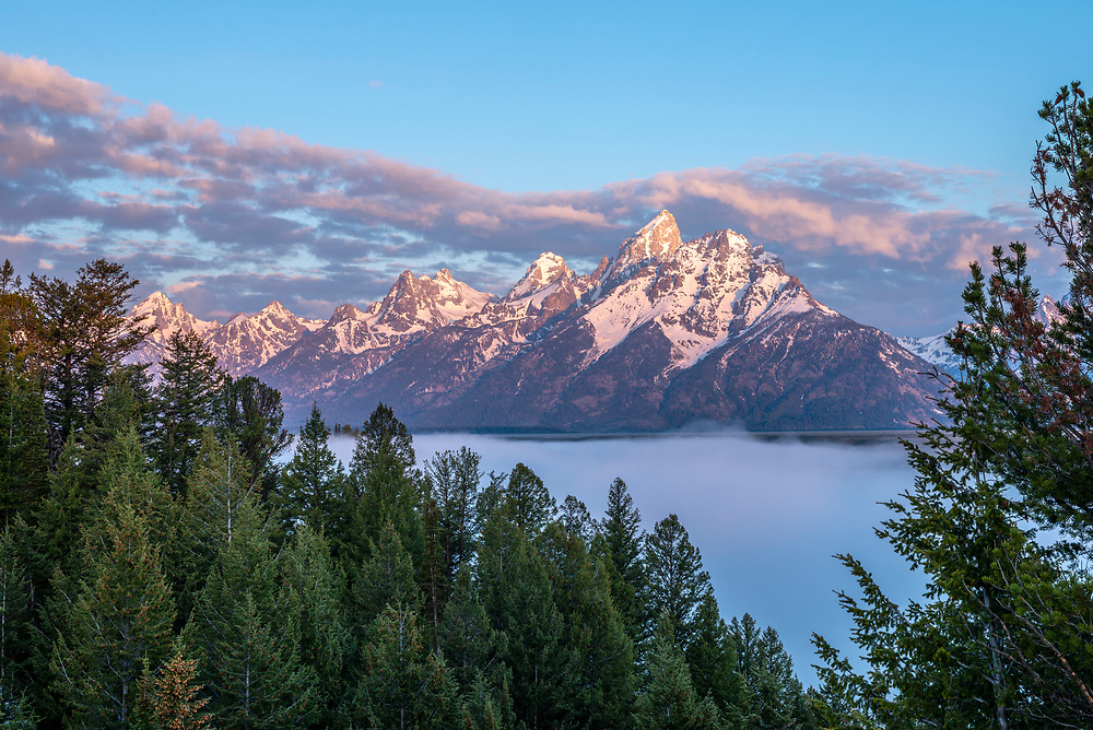 """Snake River Overlook with the Grand Teton Peak at 13776 ft (4199 meters) stands high above a fog shrouded Snake River in The Teton Range which is a mountain range of the Rocky Mountains in North America. A north-south range, it is on the Wyoming side of the state's border with Idaho, just south of Yellowstone National Park. Most of the range is in Grand Teton National Park.<br /> <br /> Early French Voyageurs used the name """"les Trois Tétons"""" (the three breasts). It is likely that the Shoshone people once called the whole range Teewinot, meaning """"many pinnacles"""". Licensing and Open Edition Prints"""