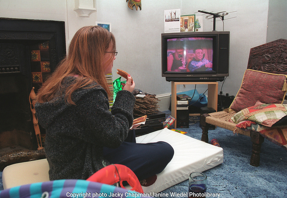 Young woman eating snack meal in front of television .