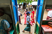 15 JUNE 2013 - YANGON, MYANMAR: Passengers walk on a station platform as the Yangon Circular train rolls through a station near Yangon. The Yangon Circular Railway is the local commuter rail network that serves the Yangon metropolitan area. Operated by Myanmar Railways, the 45.9-kilometre (28.5mi) 39-station loop system connects satellite towns and suburban areas to the city. The railway has about 200 coaches, runs 20 times and sells 100,000 to 150,000 tickets daily. The loop, which takes about three hours to complete, is a popular for tourists to see a cross section of life in Yangon. The trains from 3:45 am to 10:15 pm daily. The cost of a ticket for a distance of 15 miles is ten kyats (~nine US cents), and that for over 15 miles is twenty kyats (~18 US cents). Foreigners pay 1 USD (Kyat not accepted), regardless of the length of the journey.     PHOTO BY JACK KURTZ