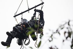 Wendover, UK. 10th October, 2021. Enforcement agents from the National Eviction Team (NET) use a cherry picker to attempt to evict environmental activists opposed to the HS2 high-speed rail link from Wendover Active Resistance (WAR) camp. WAR camp, which contains tree houses, tunnels, a cage and a 15-metre tower, is currently the largest of the protest camps set up by Stop HS2 activists along HS2's Phase 1 route between London and Birmingham.