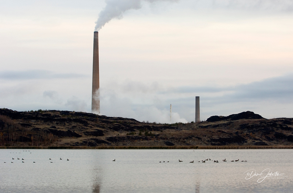 INCO/CVRD Superstack reflected in Kelly Lake, with migrating waterfowl, Sudbury, Ontario, Canada