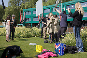 24 hours before the royal marriage of Prince William and Kate Middleton, members of an NBC TV crew stand on the grass opposite Buckingham Palace after a live broadcast for Good Morning America and a picture of the royal couple appear on a bag on the ground. Taking place on Friday 30th April in front of millions of Britons and foreign tourists (many American), the crowds are already gathering to claim their ideal locations in the front rows along the procession route.